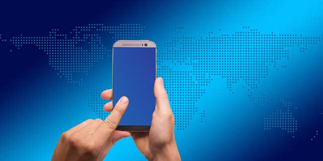 person holding a smartphone in front of blue world map background